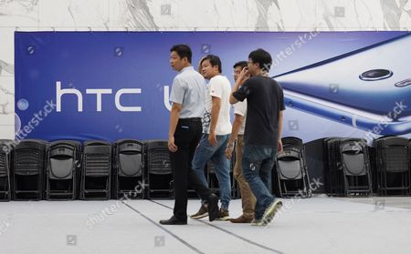 Stock Image of Staff members walk past a sign promoting HTC's latest smartphone HTC U11 at HTC Inc headquartes in Hsintien, New Taipei City, Taiwan, 21 September 2017. During the HTC Google, Joint News Conference the companies announced that they have signed an agreement under which, Google will pay HTC 1.1 billion US dollars for receiving two thousand HTC smartphone research and design engineers - half of HTC's designing team - and will secure a non-exclusive license for HTC intellectual property. Cher Wang said HTC will use more advanced technology to develop flagship smartphones and virtual reality device VIVE. Rick Osterloh said HTC has been a Google partner for a long time. He welcomes HTC membes to join Google to fuel innovation and product development in consumer hardware.