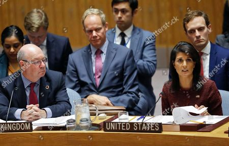 British Minister of State for the Department for International Development Alistair Burt, left, listens as U.S. United Nations Ambassador Nikki Haley address a meeting of the U.N. Security Council during the U.N. General Assembly, at U.N. headquarters