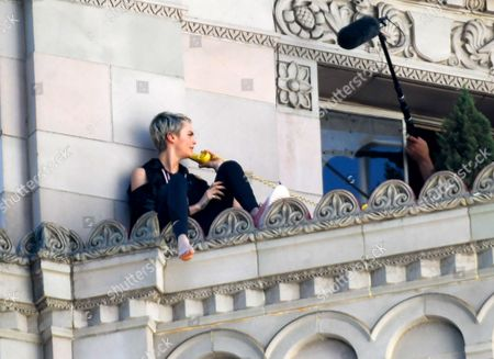 Cara Delevingne is seen on the ledge of a high rise during a photoshoot for Puma and Milk Studios with photographer Cass Bird