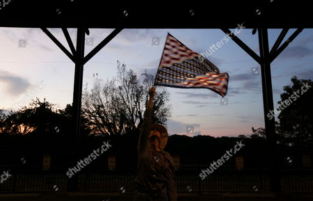 Janie Wall, of Montgomery, Ala., waves a flag before former Alaska Gov. Sarah Palin speaks at a rally, in Montgomery, Ala. Palin is in Montgomery to support support of Judge Roy Moore for the U.S. Senate candidacy