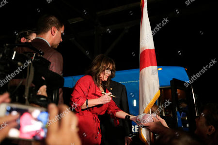 Former Alaska Gov. Sarah Palin gives an autograph after she spoke at a rally, in Montgomery, Ala. Palin is in Montgomery to support of Judge Roy Moore's candidacy for the U.S. Senate