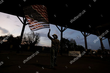 Janie Wall, of Montgomery, Ala., waves a flag before former Alaska Gov. Sarah Palin speaks at a rally, in Montgomery, Ala. Palin is in Montgomery to support of Judge Roy Moore's candidacy for the U.S. Senate