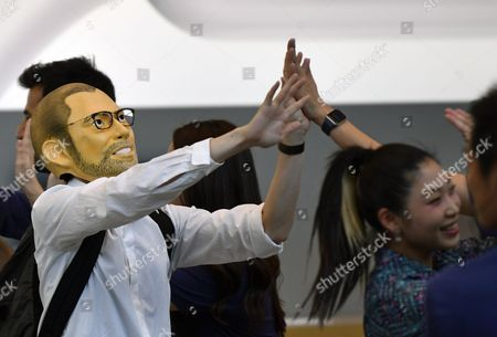 A customer wearing a mask representing Apple's co-founder Steve Jobs gives high-five with Apple store employees at the Apple Store of Omotesando shopping district in Tokyo, Japan, 22 September 2017. Apple launched its new iPhone 8 and iPhone 8 Plus and the Apple Watch Series 3 on 22 September.