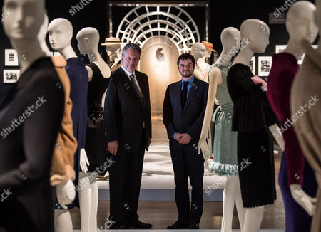 Audrey Hepburn's sons, Sean Hepburn-Ferrer and Luca Dotti standing with a collection of their mother's dresses