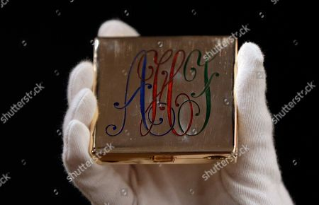 A monogramed powder compact by Ciaadetti owned by the iconic actress Audrey Hepburn on display at Christie's auction house in London, . Hepburn's sons Luca Dotti and Sean Hepburn-Ferrer are jointly selling some of their mothers personal possessions at auction on Sept. 27. The monogram is lettered AHF for Audrey Hepburn-Ferrer. It is expected to sell for some 2-3,000 pounds (US$ 2,700-4000