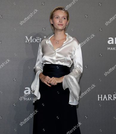 Caterina Shulha poses for photographers as she arrives for the amfAR charity dinner during the fashion week in Milan, Italy