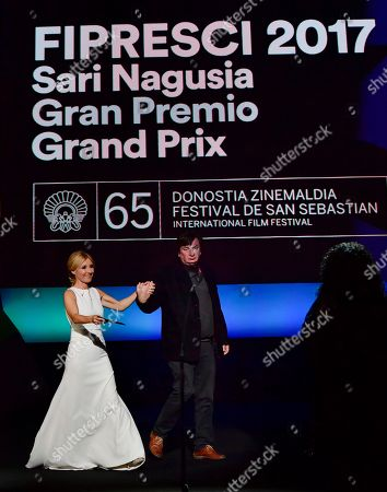Stock Picture of Aki Kaurismaki, Cayetana Guillen. Finland film director Aki Kaurismaki arrives on stage accompanied by Spanish actress Cayetana Guillen to receive the FIPRESCI Award for his film, ''The Other Side of Hope'', during the opening ceremony for the 65th San Sebastian Film Festival, in San Sebastian, northern Spain
