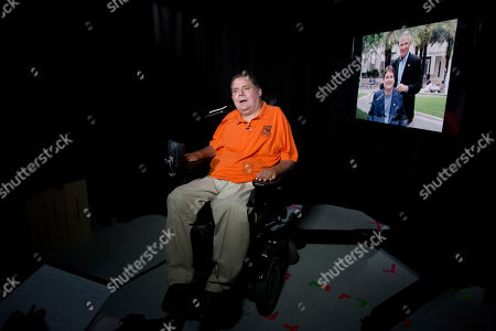 Marc Buoniconti talks during an interview in New York. On the right is a photograph of the former Citadel player with his father, Nick Buoniconti. Buoniconti wants to see youth football banned. A former college player who was paralyzed during a game and now a spokesman for the Miami Project, Buoniconti believes children's brains are put in jeopardy with every hit