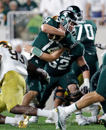 Brian Lewerke, Jay Hayes. Michigan State quarterback Brian Lewerke (14) runs for a first down as Notre Dame's Jay Hayes (93) defends during the first quarter of an NCAA college football game, in East Lansing, Mich