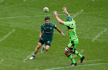 James Marshall of London Irish kicks the ball over Michael Paterson of Northampton Saints