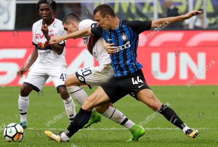 Genoa's Aleandro Rosi, center, and Inter Milan's Ivan Perisic fight for the ball during a Serie A soccer match between Inter Milan and Genoa, at Milan's San siro Stadium, northern Italy