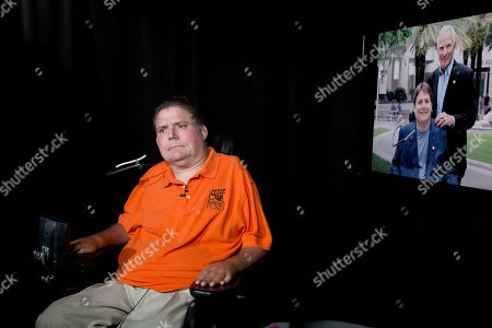 """Marc Buoniconti talks during an interview in New York. On the right is a photograph of the former Citadel player with his father, Nick Buoniconti. Marc Buoniconti has been confined to a wheelchair for 32 years. Through those decades his father Nick has been his companion. Marc calls Nick his """"savior."""" Now it is Nick who needs Marc's inspiration"""