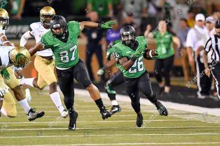 North Texas Mean Green running back Evan Johnson (26) runs a kick return for 40 yards as North Texas Mean Green tight end Kelvin Smith (87) blocks to setup a game wining field goal during an NCAA Football game between the Univerisity Alabama Birmingham Blazers and the North Texas Mean-Green Eagles at Apogee Stadium in Denton, Texas