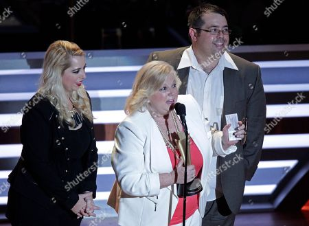 Stock Photo of Terri Hollowell, wife of Jeff Walker accepts the Jim Reeves International Award, awarded posthumously to Jeff Walker with her are children Jon Walker and Christy Walker-Watkins at 10th Annual ACM Honors at Ryman Auditorium, in Nashville, Tenn