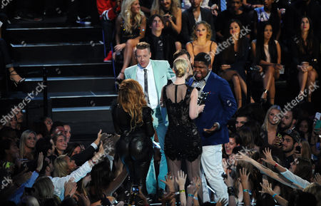 """From background left, Macklemore, Ryan Lewis, and Ray Dalton accept the award for best hip hop video for """"Can't Hold Us"""" at the MTV Video Music Awards, at the Barclays Center in the Brooklyn borough of New York"""