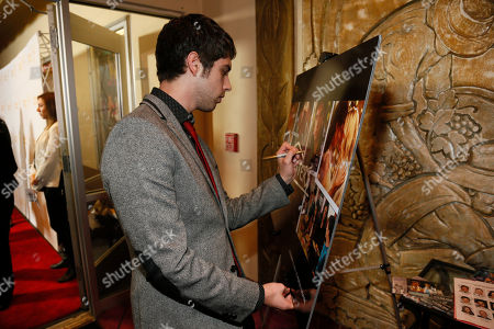 """Actor David Lambert signs a poster during """"An Evening with the Fosters"""" presented by the Television Academy at the El Portal Theatre on in the NoHo Arts District in Los Angeles"""