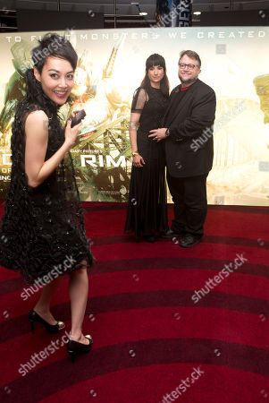 Actress Rinko Kikuchi, left, reacts after photographing Director Guillermo Del Torro, right and his wife Lorenza Newton as they arrive for the UK Premiere of Pacific Rim, at the BFI southbank, in central London