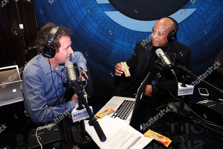 Stock Photo of Football legend Ronnie Lott, right, visits Jim Rome with CBS Sports Radio on Radio Row in New York on to talk about the new Butterfinger Peanut Butter Cups debut at the big game