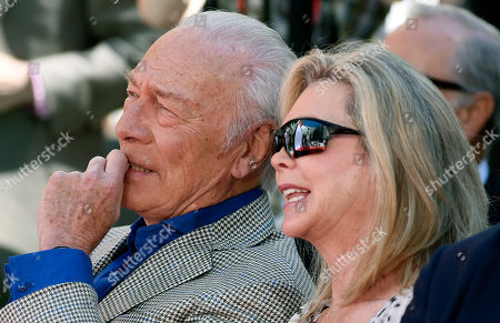 Stock Photo of Actor Christopher Plummer, left, and his wife Elaine Taylor listen to actress Shirley MacLaine's speech during a hand and footprint ceremony for him outside the TCL Chinese Theatre IMAX, in Los Angeles