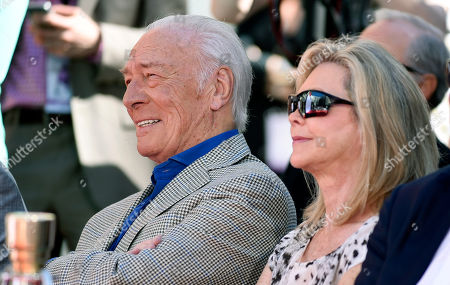 Actor Christopher Plummer, left, and his wife Elaine Taylor listen to actress Shirley MacLaine's speech during a hand and footprint ceremony for him outside the TCL Chinese Theatre IMAX, in Los Angeles