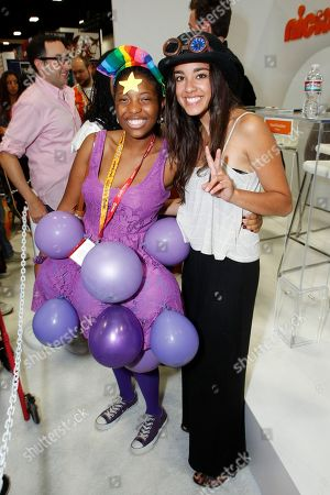 Actress Seychelle Gabriel poses for a photo with The Legend of Korra fan at Nickelodeon during Comic-Con, in San Diego, Calif