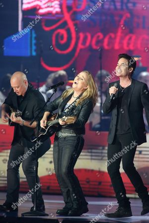 Melissa Etheridge (center) with Jimmy Stafford, left, and Pat Monahan of the band Train perform in concert during the Star-Spangled Spectacular Concert: Bicentennial of Our National Anthem at Pier Six Pavilion, in Baltimore