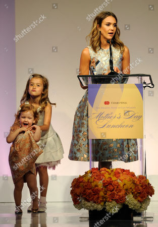 Actress Jessica Alba accepts her Mother of the Year award as her daughters Honor Marie, background, and Haven Garner look on at the 85th Helping Hand of Los Angeles Mother's Day Luncheon, Friday, May 9. 2014 in Beverly Hills, Calif