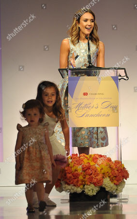 Actress Jessica Alba accepts her Mother of the Year award as her daughters Haven Garner, far left, and Honor Marie look on at the 85th Helping Hand of Los Angeles Mother's Day Luncheon, Friday, May 9. 2014 in Beverly Hills, Calif