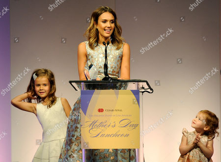 Actress Jessica Alba accepts her Mother of the Year award as her daughters Honor Marie, left, and Haven Garner look on at the 85th Helping Hand of Los Angeles Mother's Day Luncheon, Friday, May 9. 2014 in Beverly Hills, Calif