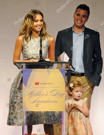 Actress Jessica Alba accepts her Mother of the Year award as her husband Cash Warren, right, and their daughter Haven Garner look on at the 85th Helping Hand of Los Angeles Mother's Day Luncheon, Friday, May 9. 2014 in Beverly Hills, Calif