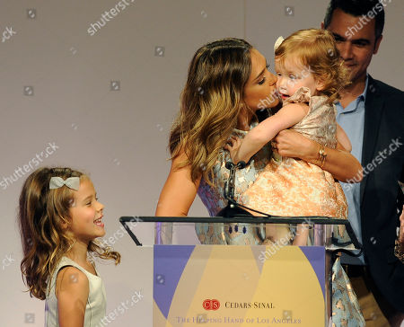 Actress Jessica Alba gives her daughter Haven Garner a kiss as she accepts her Mother of the Year award at the 85th Helping Hand of Los Angeles Mother's Day Luncheon, Friday, May 9. 2014 in Beverly Hills, Calif. Looking on are Alba's husband Cash Warren and their older daughter Honor Marie