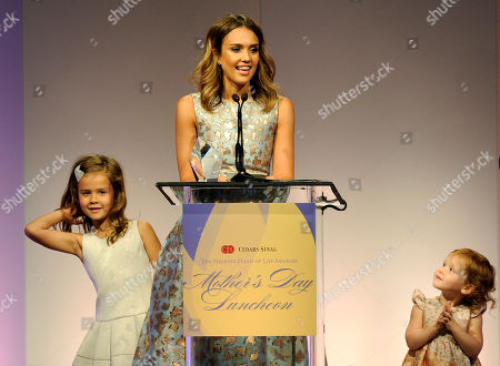 Actress Jessica Alba accepts her Mother of the Year award as her daughters Honor Marie, left, and Haven Garner look on at the 85th Helping Hand of Los Angeles Mother's Day Luncheon, in Beverly Hills, Calif