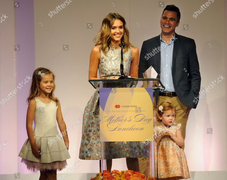 Actress Jessica Alba accepts her Mother of the Year award as her husband Cash Warren and their daughters Honor Marie, left, and Haven Garner look on at the 85th Helping Hand of Los Angeles Mother's Day Luncheon, Friday, May 9. 2014, in Beverly Hills, Calif