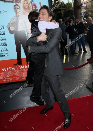 Zach Braff, right, hugs Pierce Gagnon as they arrive at the Los Angeles premiere of 'Wish I Was Here' at the Directors Guild of America Theater on