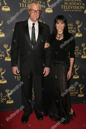 John Tesh, left, and Connie Sellecca arrive at the 2015 Daytime Creative Arts Emmy Awards at The Universal Hilton, in Universal City, Calif