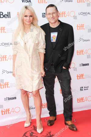 """Executive producer Pamela Anderson, left, and Avi Lewis attend a premiere of """"This Changes Everything """" on day 4 of the Toronto International Film Festival at the the Ryerson theatre, in Toronto"""