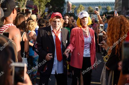 Husband and wife Dave Hester and Donna Hester, dressed as zombie Donald Trump and zombie Hillary Clinton, walk down Fifth Avenue as they take part in the Zombie Walk on day three of the Comic-Con International held at the San Diego Convention Center in San Diego
