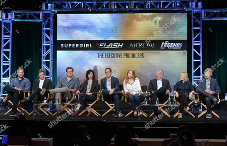 Executive producers from The CW's television shows Aaron Helbing, from left, Todd Helbing, Andrew Kreisberg, Ali Adler, Greg Berlanti, Sarah Schechter, Marc Guggenheim, Wendy Mericle and Phil Klemmer participate in a panel during the network's Television Critics Association summer press tour, in Beverly Hills, Calif