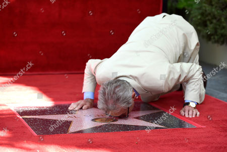 Recording and mix engineer Al Schmitt leans down to kiss his star during the ceremony honoring him with a star on the Hollywood Walk of Fame, in Los Angeles