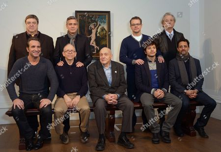 Cast members of the film The Monuments Men pose during a photocall in front of 'Cupid Complaining To Venus', by Lucas Cranach the Elder, believed to be from Adolf Hitler's private collection, at the National Gallery, in London, . From left to right seated, French actor Jean Dujardin, US actor Bob Balaban, real life 'monument man' Harry Ettlinger, British actor Dimitri Leonidas and US actor Grant Heslov. In background from left to right, US actors, John Goodman, George Clooney, Matt Damon and Bill Murray