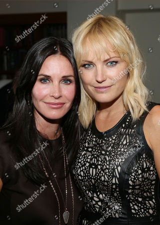 Courteney Cox, left, and Malin Akerman pose for a photo as Justin Theroux and Dan Peres celebrate the August issue of DETAILS at The Sunset Tower Hotel on in West Hollywood, Calif