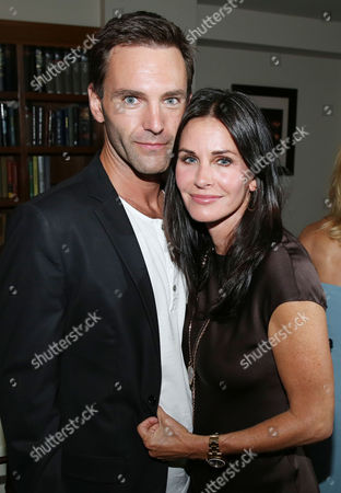 Courteney Cox, right, and Johnny McDaid pose for a photo as Justin Theroux and Dan Peres celebrate the August issue of DETAILS at The Sunset Tower Hotel on in West Hollywood, Calif