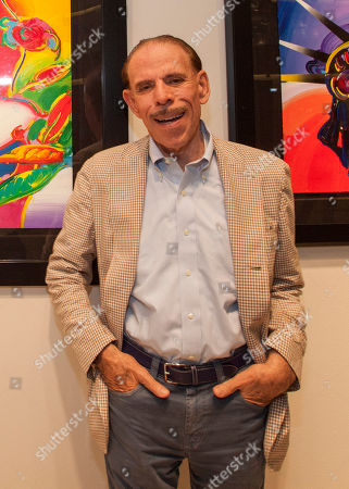 Artist Peter Max poses for a photo during his retrospective with the Road Show Company exhibit at Northbrook Court mall, in Northbrook, Ill