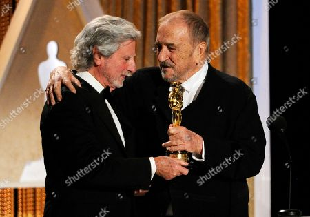 """French screenwriter Jean-Claude Carriere, right, receives his Honorary Oscar from director Philip Kaufman during the 2014 Governors Awards, in Los Angeles. Carriere and Kaufman worked together on the 1988 film """"The Unbearable Lightness of Being"""