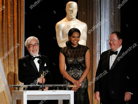 Japanese animator/director Hayao Miyazaki, left, accepts his Honorary Oscar as John Lasseter, far right, chief creative officer at Pixar, Walt Disney Animation Studios and DisneyToon Studios looks on during the 2014 Governors Awards, in Los Angeles