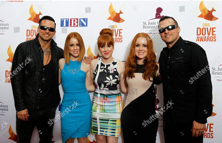 Natalie Taylor, center, Nicole Taylor, right, and Nika Taylor of the group Red Roots pose for a photo with Anthony Armstrong and Randy Armstrong of the group Red arrive at Lipscomb University for the Dove Awards, in Nashville, Tenn. Michael Barnes, guitarist Anthony Armstrong, and bassist Randy Armstrong