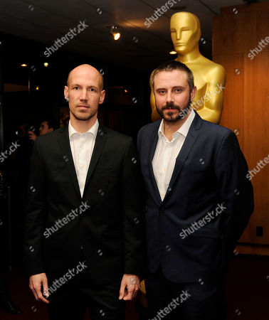 """Richard Rowley, left, director of the Oscar-nominated documentary film """"Dirty Wars,"""" and the film's co-writer and cast member Jeremy Scahill pose together at a reception featuring the Oscar nominees in the Documentary Feature and Documentary Short Subject categories, in Beverly Hills, Calif. The Oscars will be held on Sunday at the Dolby Theatre in Los Angeles"""