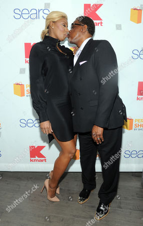 Reality TV star couple NeNe and Gregg Leakes lean in for a kiss at the Shop Your Way Personal Shopper launch in New York
