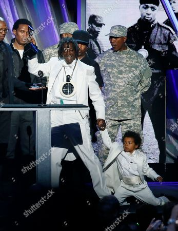 Flava Flav brings a young boy with him to the podium as he speaks while Public Enemy is inducted into the Rock and Roll Hall of Fame during the Rock and Roll Hall of Fame Induction Ceremony at the Nokia Theatre on in Los Angeles