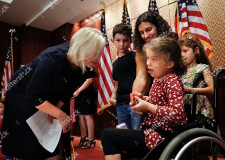Kristen Gillibrand, Jaime Davis Smith, Claire Smith, Ben Smith, Sarah Smith. Senator Kirsten Gillibrand, D-N.Y., left, stops to talk with Jamie Davis Smith, and her children from left, Ben, 9, Claire 11, and Sarah, 7, following a news conference to oppose GOP's Graham-Cassidy health care repeal strategy, on Capitol Hill in Washington